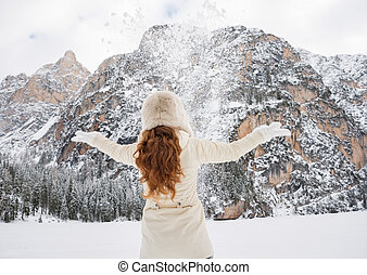 Seen from behind woman in coat and hat throwing snow...