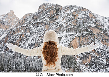 Seen from behind young woman rejoicing in winter outdoors