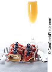 sweet crepes with mimosa - breakfast against white...