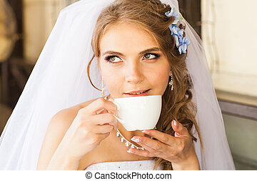 bride drinking coffee in cafe. Wedding day