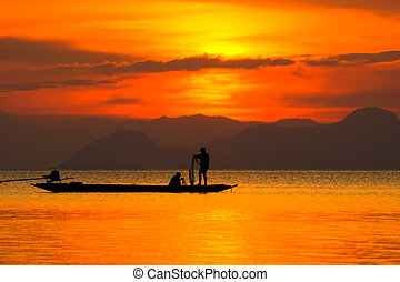 Silhouettes of fisherman at the lake with sunset, Thailand.