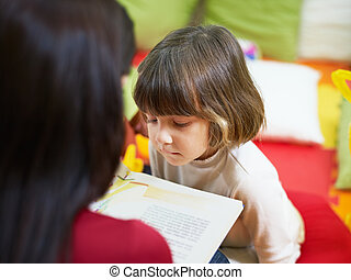 female teacher reading book to little girl