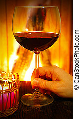 Drinking glass of red wine by the fireplace