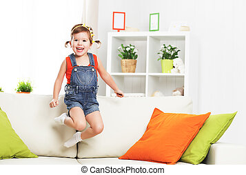 happy child girl playing and jumping on couch at home -...