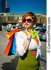 Young beautiful woman with bags after shopping in the...