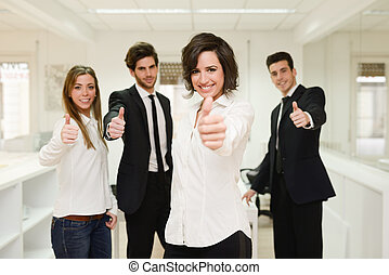 Cheerful business group giving thumbs up - Portrait of...