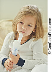 girl with cough - little girl with cough using inhaler at...