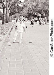 first steps - baby girl walking by the street her first...