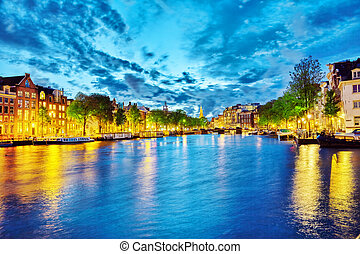 Famous Amstel river and night view of beautiful Amsterdam...