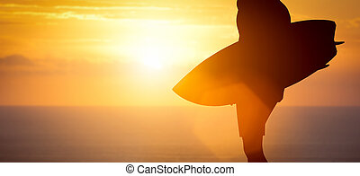 Surfer standing with his surfboard on the beach at sunset...