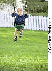 Boy on swing - Happy boy playing on outdoor swing