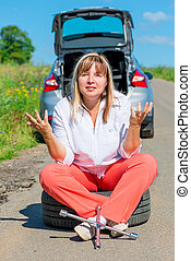 annoyed woman sitting on the bursting of the wheel and waiting for help