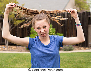 Bad hair day - Teenager holding up messy hair in playful...