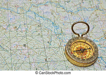 Compass and map. The magnetic compass is lying on a...