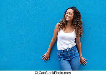 Young woman smiling against blue background