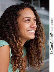 Smiling young woman looking away - Close up portrait of...