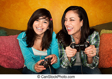 Hispanic Woman and Girl Playing Video game - Attractive...