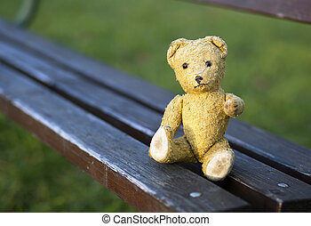 Toy bear sitting on a bench and giving paw for help