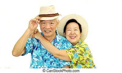 Happy Asian senior couple hugging happily wearing hat ready...