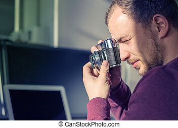 Hipster young man holding a vintage camera and taking a...