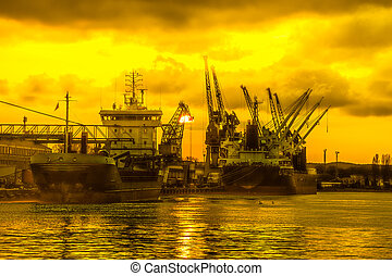 Port at sunset - Silhouettes of cranes and ships in port of...