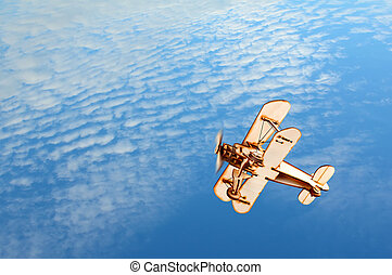 Wooden toy airplane in the blue sky