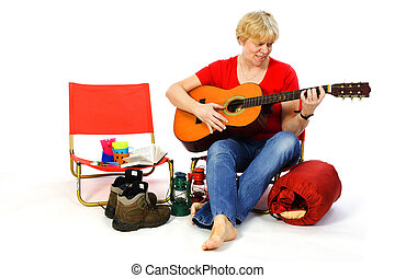 Playing guitar at the campground - Senior woman is playing...