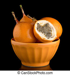 Passion fruit maracuja granadilla on ceramic yellow bowl,...