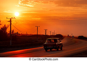 Oldtime cars go on the road near oil derricks at sunset,...
