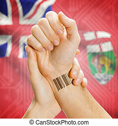 Barcode ID number on wrist with Canadian province flag on...
