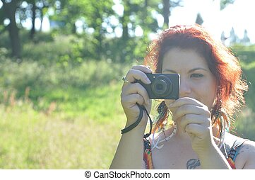 woman taking picture  in a park