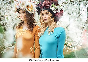 Two beautiful women in the summer orchard