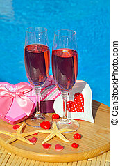 Glasses with red champagne and starfish on swimming pool...