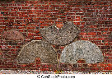 Brick wall with embedded millstones. - Architectural pattern...