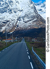 Asphalt road in Norvegian snowbound mountains