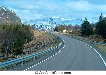 Grey asphalt road in Norvegian mountains in summer day