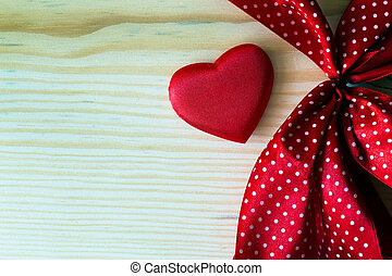 valentine heart with red dotted ribbon on a wooden...