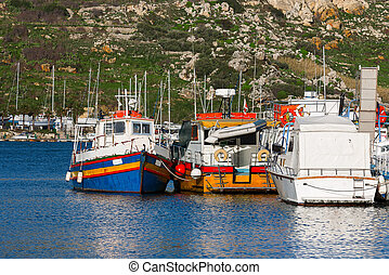 Colorful traditional fisher boats at a pier. Port of Mgarr,...