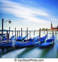 Venice, gondolas or gondole on sunset and church on...