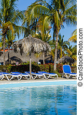 Pool, sun chairs and palm trees in an all inclusive hotel -...