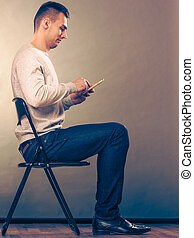 Man using mobile phone sitting in chair. Absorbed male...