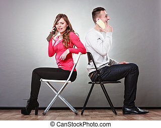 Young couple talking on mobile phones. - Young couple...