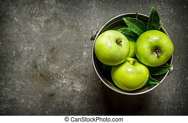 Fresh green apples in the bucket. On rustic stone...