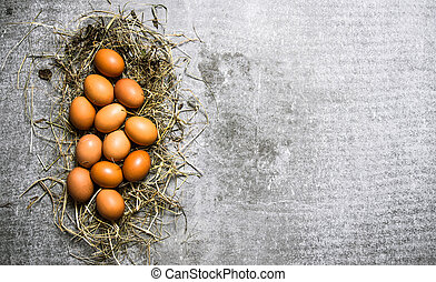 A set of eggs in the hay. On stone background. - A set of...