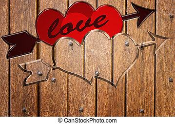 love - wood carving in the shape of red two hearts and arrow...