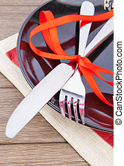 Table setting with red ribbon on black plate on wooden