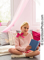Girl with book sitting on the bed