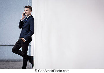 Businessman leaning against wall - Young businessman is...