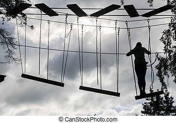 Silhouette of the girl on Dangerous ropeway with tether in rope