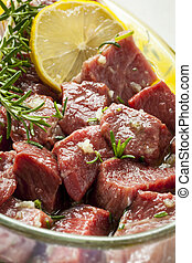 Raw Beef Marinating with Lemon, Oil and Herbs